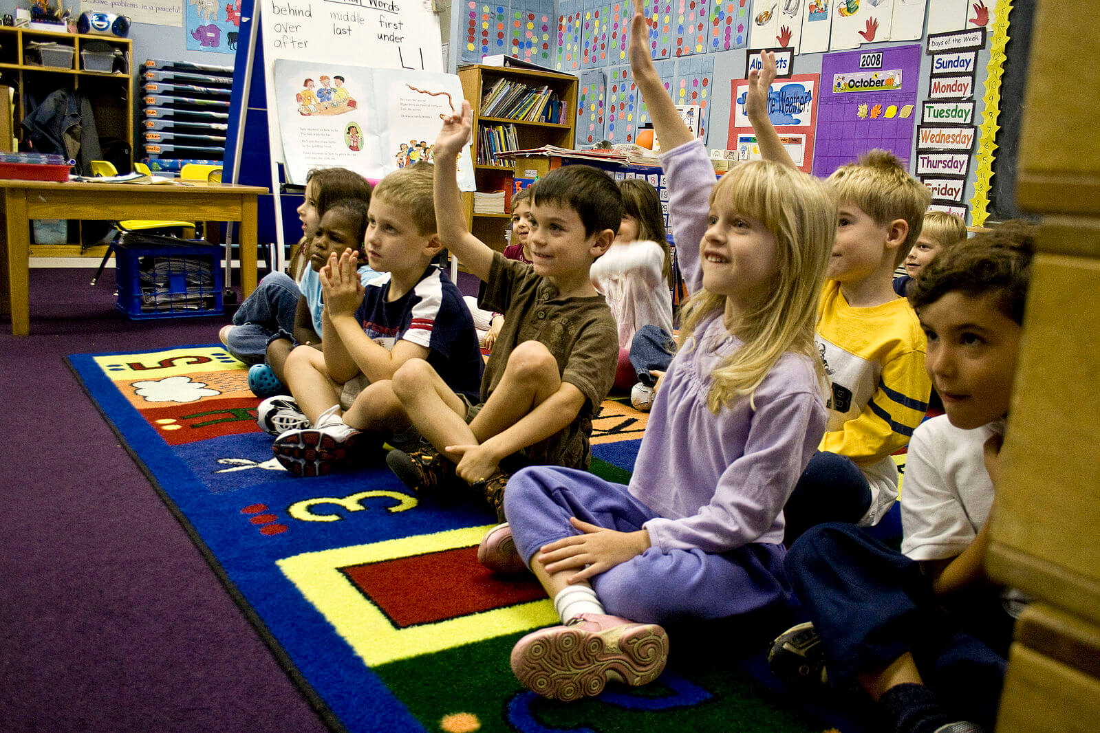 student teaching in kindergarten with students raising their hands while sitting on the rug - student teaching tips