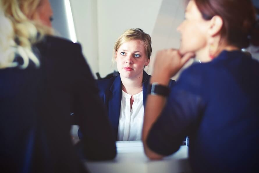Women thinks about questions to ask at a teaching interview